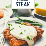 Chicken fried steak on a plate with green beans and text title overlay
