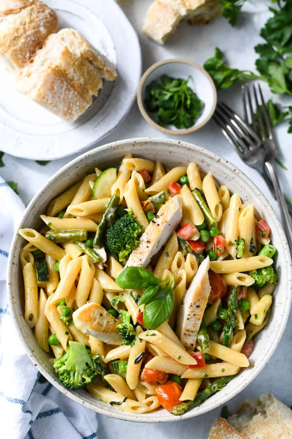 Overhead shot of a bowl of pasta primavera with cream sauce and a side of bread