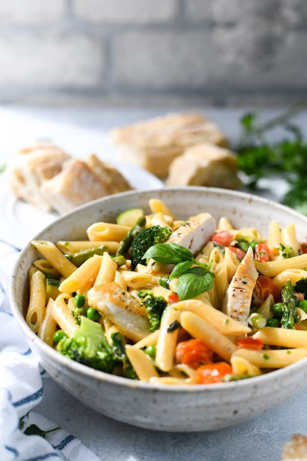Front shot of a bowl of chicken primavera on a white table with baguette in the background