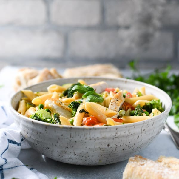 Square image of a bowl of chicken primavera alfredo on a white table with a side of bread and fresh herbs garnish