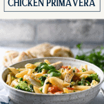 Creamy chicken primavera in a bowl with text title box at top