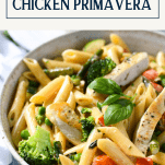 Close up front shot of a bowl of pasta primavera with chicken and asparagus and a text title box at top
