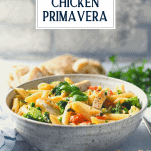 Bowl of chicken pasta primavera on a table with text title overlay
