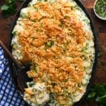 Overhead shot of a cheesy chicken and broccoli casserole with rice on a wooden cutting board