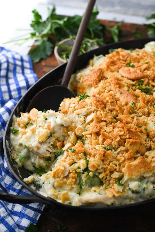 Close up side shot of chicken broccoli and rice casserole recipe with a wooden serving spoon