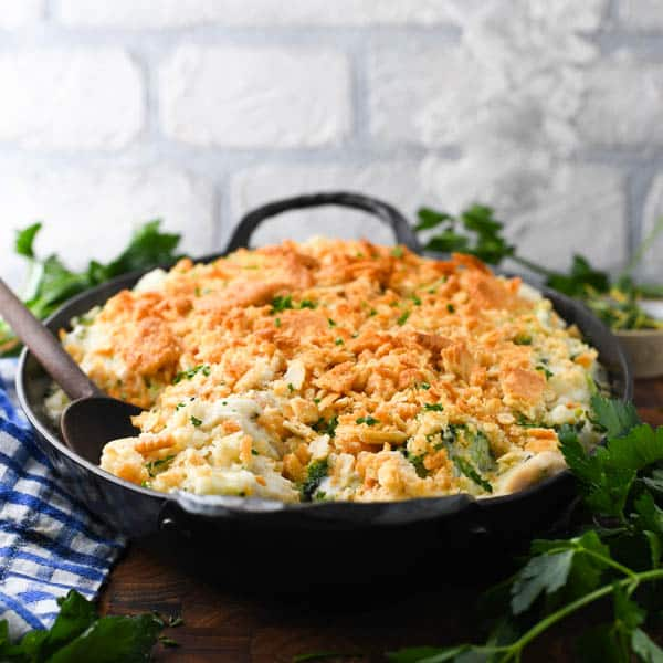 Front shot of chicken broccoli rice casserole in a dish with a wooden spoon in front of a white brick wall