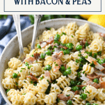Close up side shot of a bowl of creamy chicken pasta with bacon lemon and peas and a text title box at top