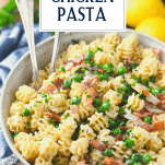 Close up image of a bowl of creamy chicken and bacon pasta with text title overlay