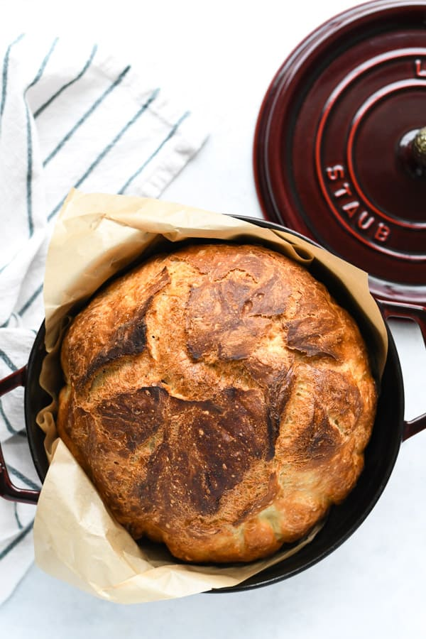 Overhead image of cast iron Dutch oven bread with a blue and white striped towel nearby
