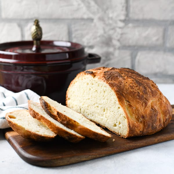 Square shot of a loaf of quick Dutch oven bread sliced on a wooden board