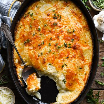 Long overhead shot of Potatoes Au Gratin in a baking dish with silver serving spoon