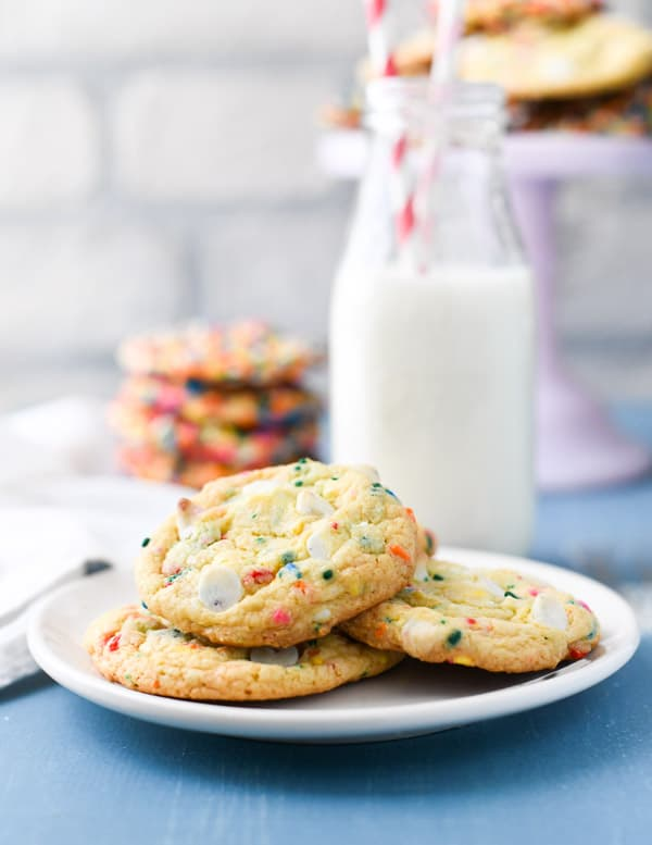 Plate of confetti cookies with milk in the background