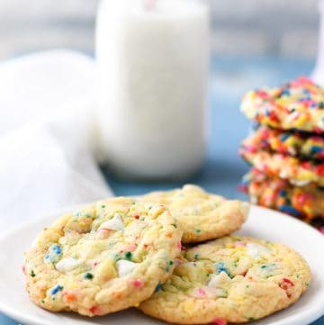 Side shot of a white plate full of funfetti chip cookies