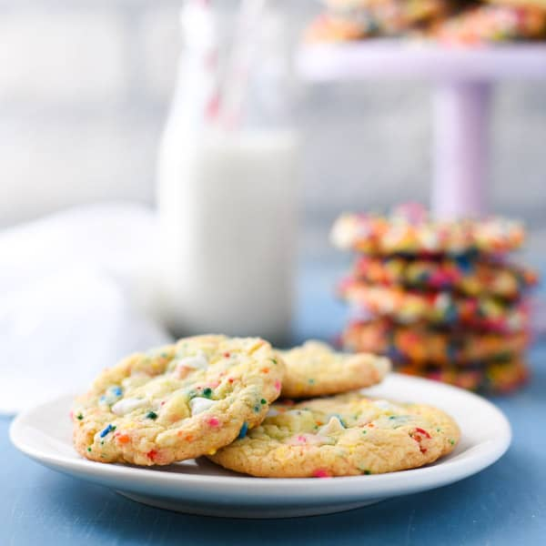 Side shot of a plate of funfetti cake mix cookies on a plate with milk in the background