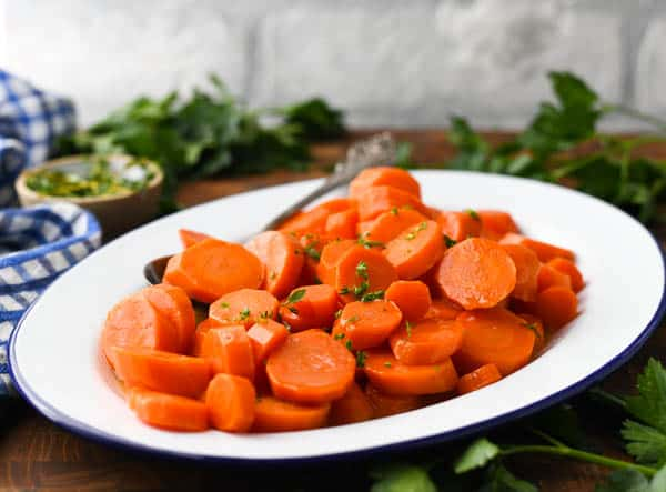Horizontal shot of glazed carrots on a white oval dish with blue trim