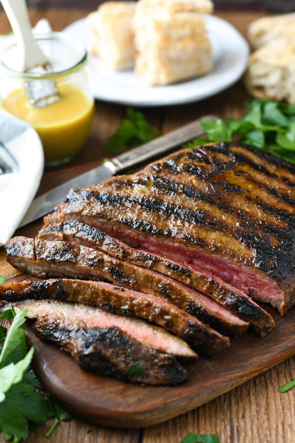 Front shot of sliced marinated and grilled flank steak on a cutting board with bread and herbs in the background