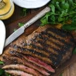 Overhead image of grilled flank steak with bourbon glaze on a wooden cutting board