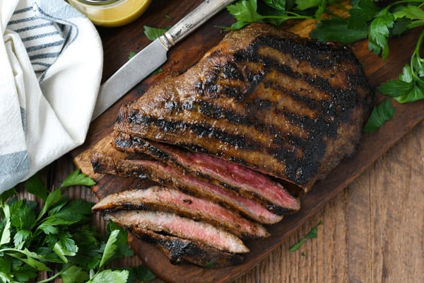 Horizontal overhead shot of sliced grilled flank steak recipe on a wooden board