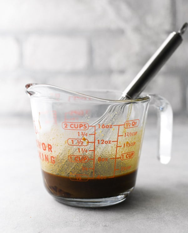 Flank steak marinade in a glass measuring cup with a whisk