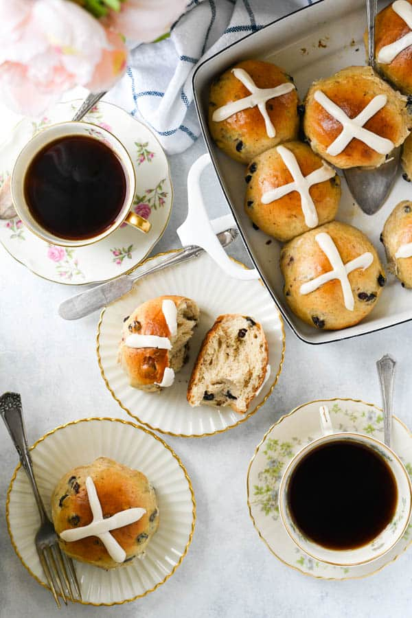 Overhead shot of easy hot cross buns recipe served on a white table with coffee