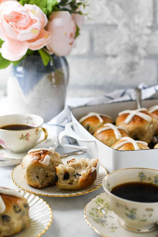 Side shot of an Easter table full of coffee and hot cross buns