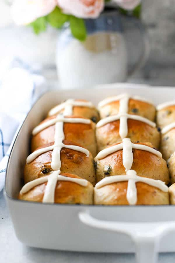 Close up front shot of an easy hot cross buns recipe prepared in a white dish on a white table