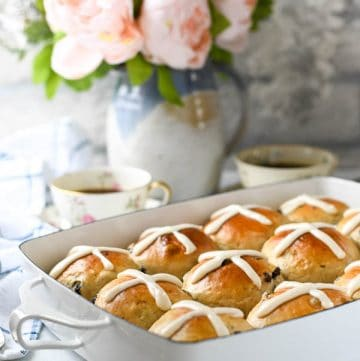 Side shot of the softest hot cross buns recipe on a white table in front of a vase of flowers