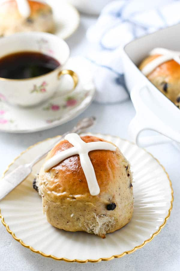 Close up side shot of an easy hot cross bun recipe served on a small plate