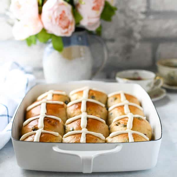 Square image of a front shot of a white dish full of make ahead hot cross buns