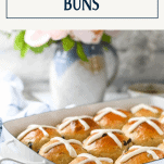 Side shot of a pan of easy hot cross buns recipe with text title box at top