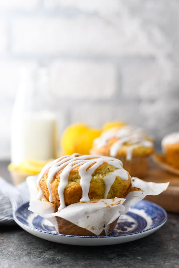 Front shot of lemon and poppy seed muffins on a blue and white plate with glaze