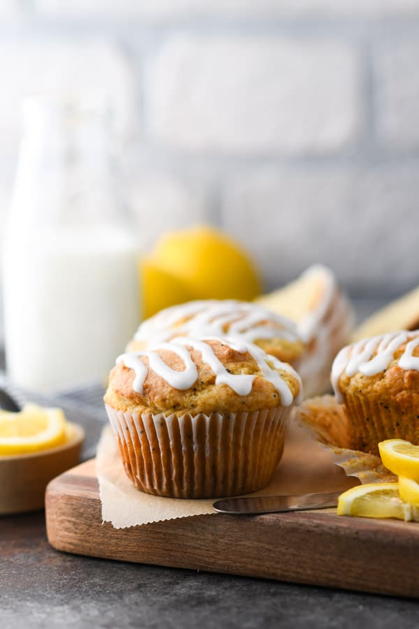 Side shot of a lemon poppy seed muffin with lemon glaze on a wooden cutting board