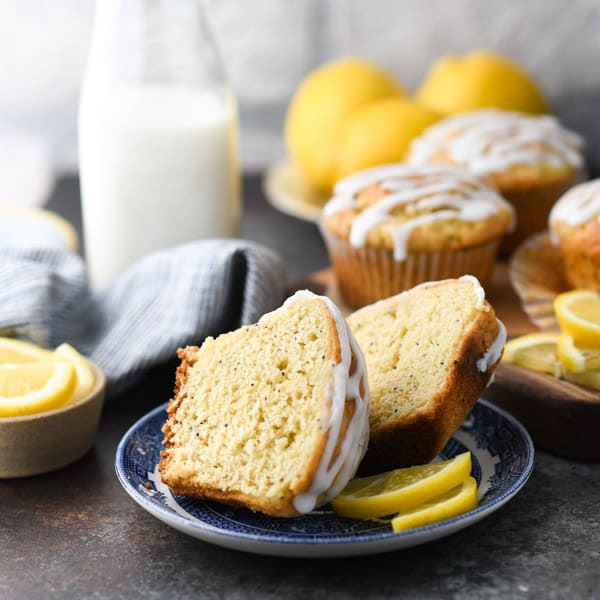 Moist and fluffy lemon poppy seed muffins cut in half on a blue and white plate