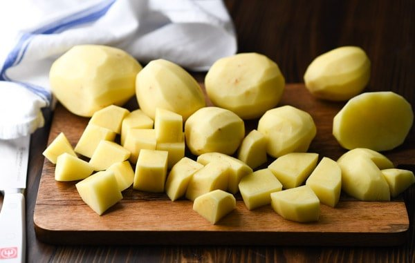 Peeled and diced potatoes on a wooden cutting board