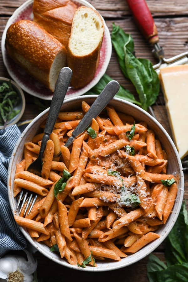 Overhead image of a bowl of the best penne alla vodka recipe with a side of bread
