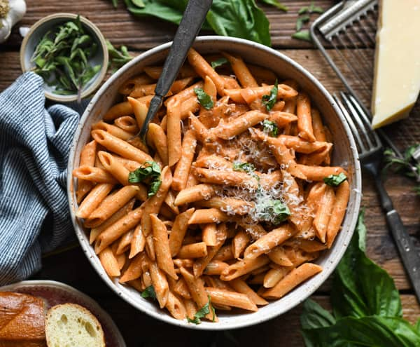 Overhead shot of a bowl of creamy penne alla vodka on a wooden table