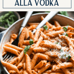 Close up shot of a bowl of creamy penne alla vodka with a text title box at top