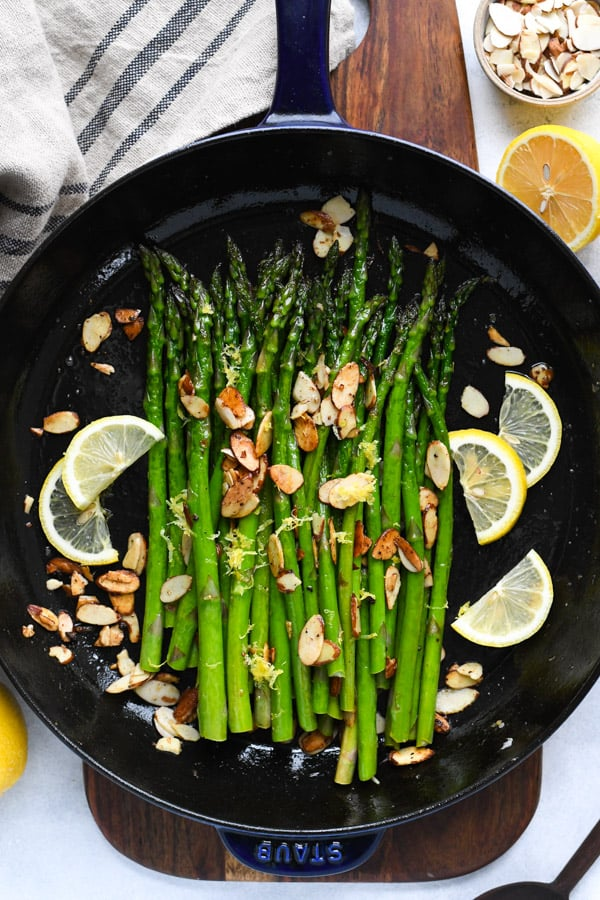 Overhead shot of pan sauteed asparagus garnished with lemon and almonds