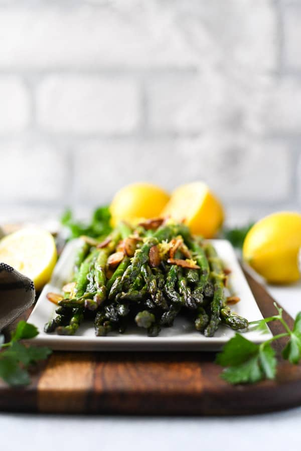 Close up front shot of the best sauteed asparagus on a white rectangular dish in front of a white brick wall