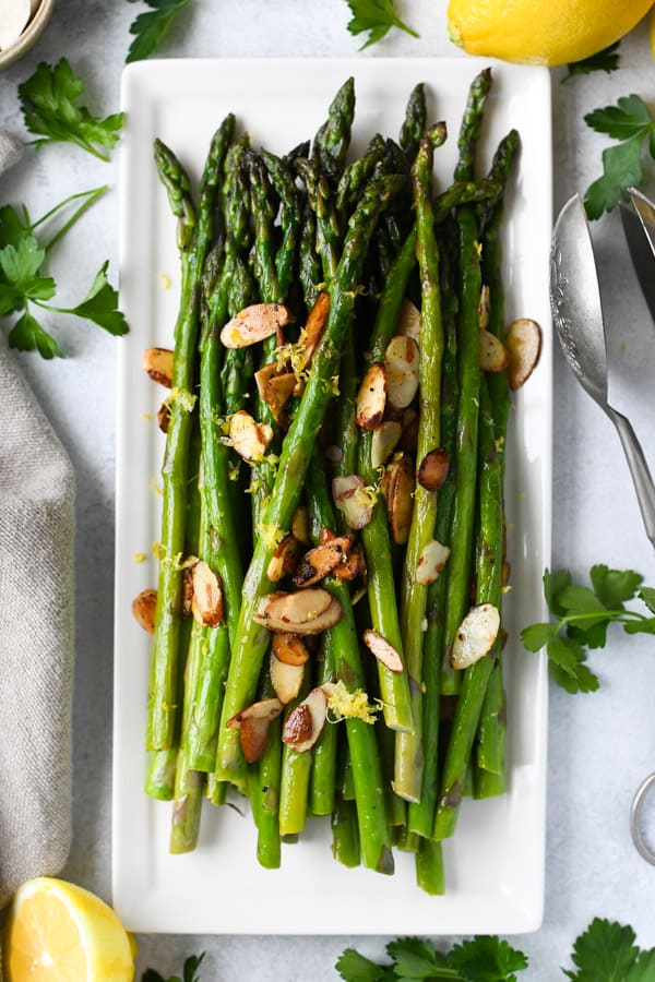 Overhead shot of sauteed asparagus with garlic lemon and almonds on a white rectangular dish.