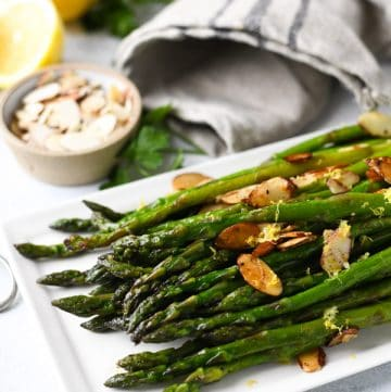 Close up side shot of sauteed asparagus with lemon and garlic on a white serving tray with toasted almonds on top