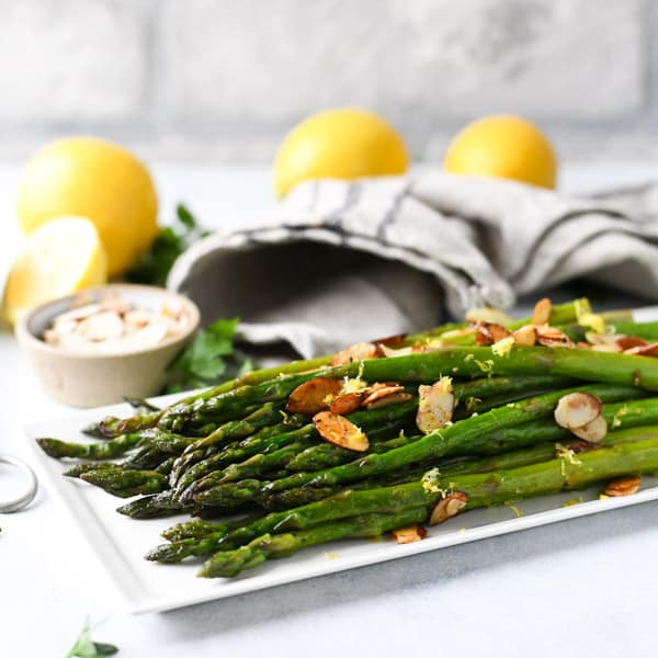 Square image of sauteed asparagus with lemon and garlic on a white tray