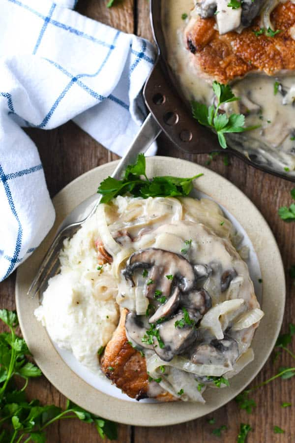 Overhead image of mushroom smothered pork chops on a plate with mashed potatoes