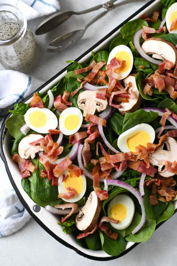 Overhead shot of a fresh spinach salad with bacon on a white table