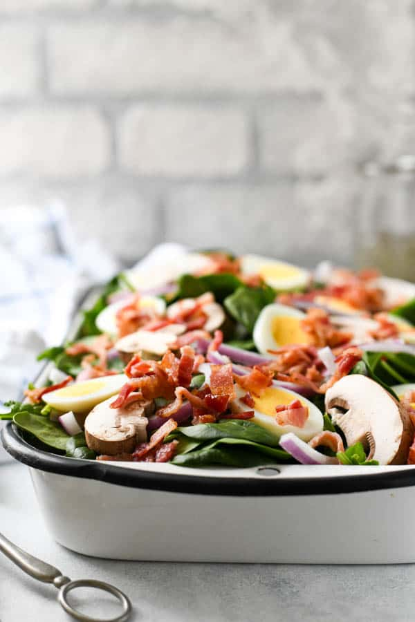 Front shot of spinach salad with bacon in front of a white brick wall