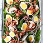Long overhead shot of a bowl of spinach salad with bacon and poppy seed dressing
