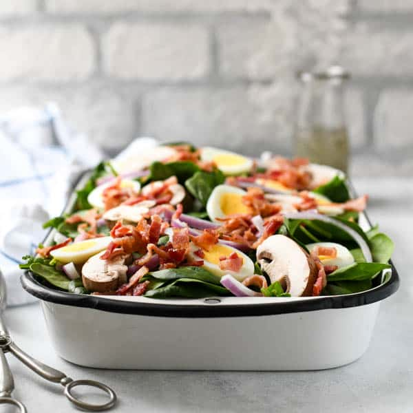 Square image of the front shot of a simple spinach salad