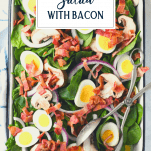 Overhead shot of spinach salad with bacon and text title overlay