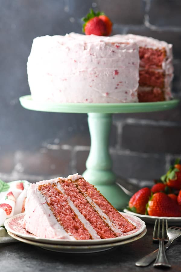 Side shot of easy strawberry cake on a green cake stand