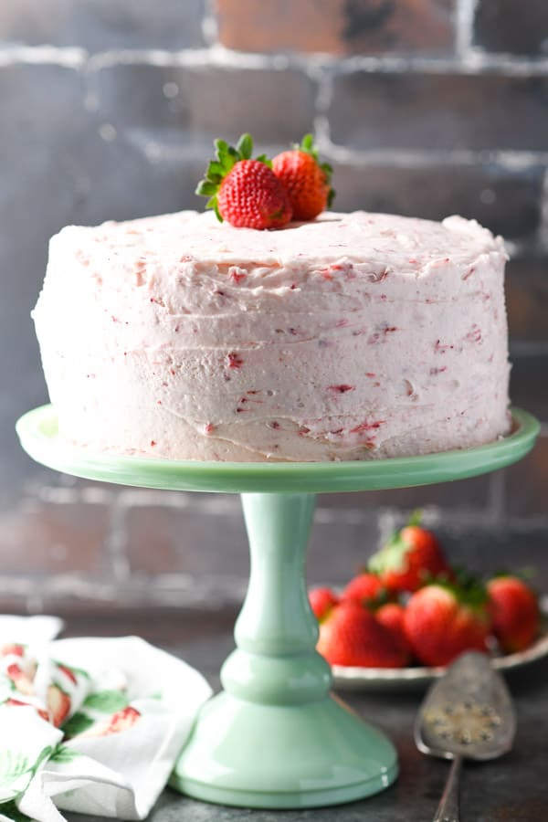 Front shot of homemade strawberry cake on a mint green cake stand
